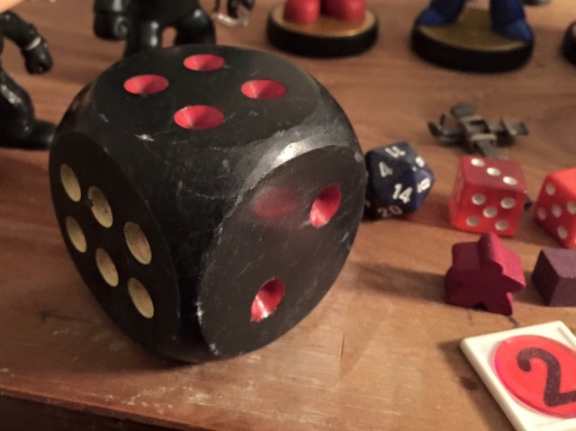 A large stone die, some dice, and toys used in the creation of games.